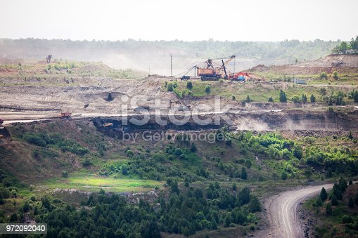istock Dump trucks at open coal mine 972092040