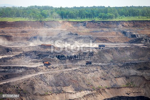 istock Dump trucks at open coal mine 972095384