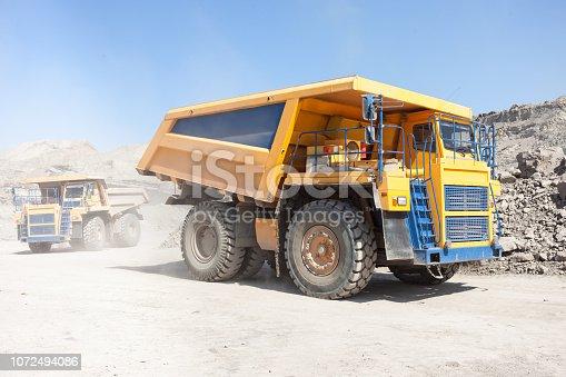 istock Dump trucks moving in a mine 1072494086