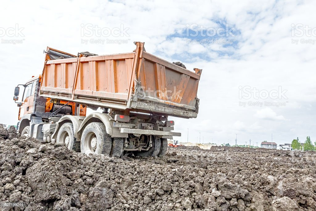 Dumper truck is going backward to unload soil stock photo