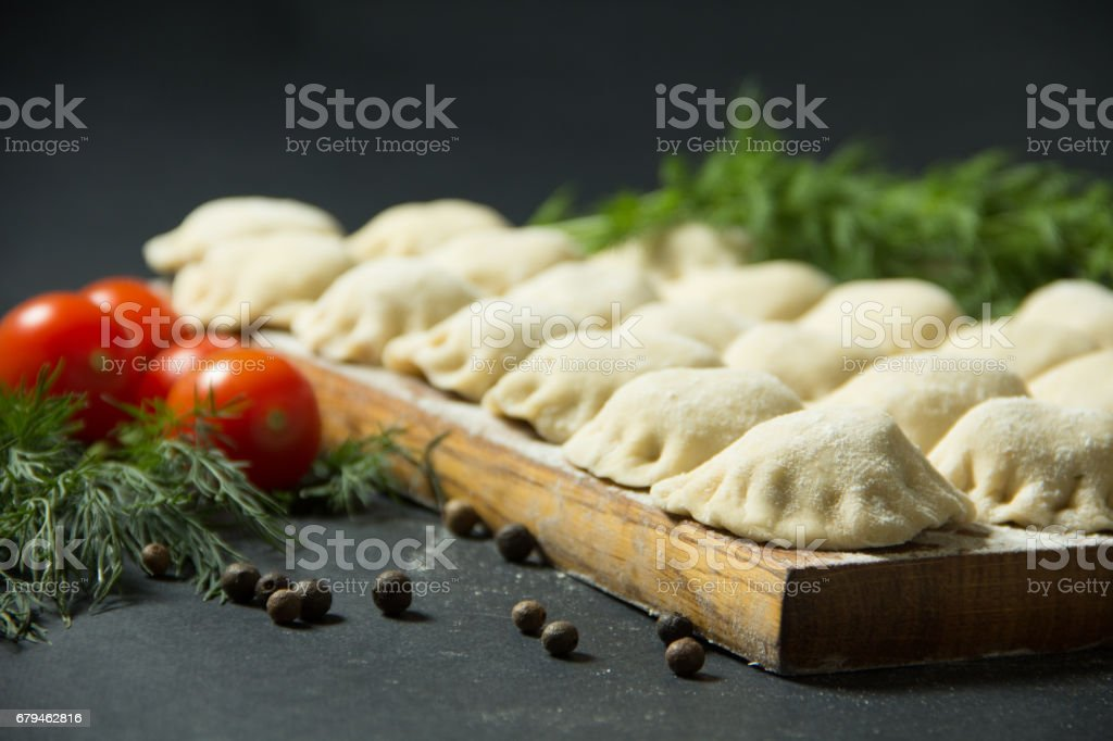 dumplings on a black background with fresh herbs and vegetables. homemade food. Traditional Russian food is pelmeni. royalty-free stock photo