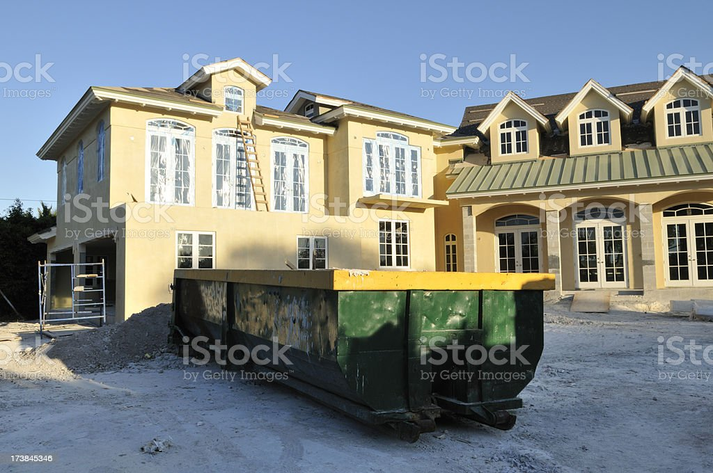 Dumpster and Construction House stock photo