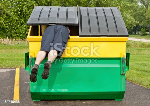 the legs and rear end of a caucasian man wearing shorts hangs out of a yellow and green dumpster