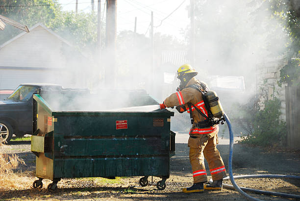 Dumpster Fire Dumpster fire in an alley in Roseburg Oregon dumpster fire stock pictures, royalty-free photos & images