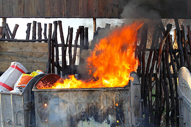 Dumpster fire Dumpster fire with heavy smoke from garbage dumpster fire stock pictures, royalty-free photos & images