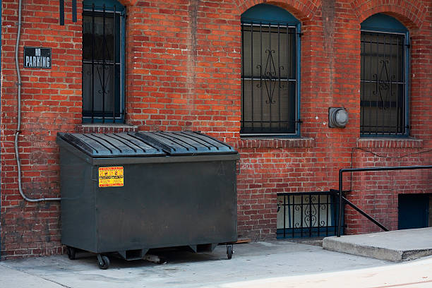 dumpster in an alley - garbage bin stock photos and pictures