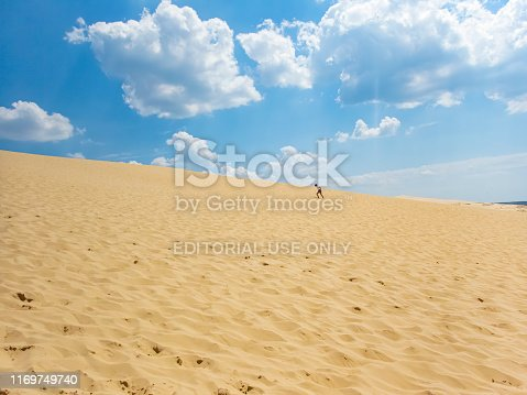 The famous Dune de Pilat in Western France near the Arcachon Basin. This shows the beach with the dunes in the foreground and fluffy white clouds in a blue summer sky. there is a young woman walking up the steep dune.