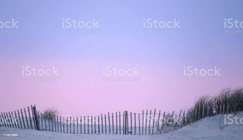 Dune Fence on the Beach with Sunset Sky stock photo