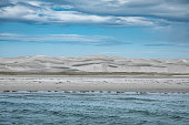 View from the gloomy sea on grey  dune shore and cloudscape, Sea of Cortes, Baja California, Mexico