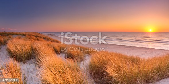 Tall dunes with dune grass and a wide beach below. Photographed at sunset on the island of Texel in The Netherlands.