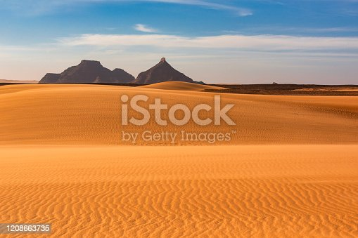 Dunes and mountains in the remote Ennedi Mountains (massif) in the Sahara desert, North-East Chad. The Ennedi massif was declared as an UNESCO World Heritage site in 2016.