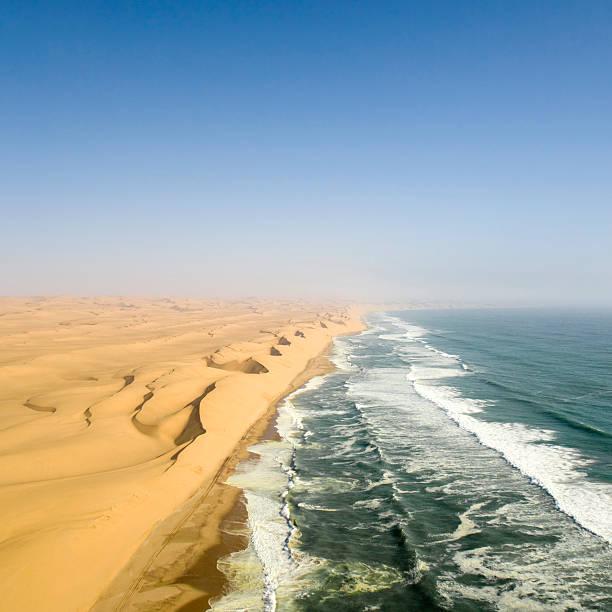 dunes from namib desert meeting atlantic ocean  namib desert stock pictures, royalty-free photos & images