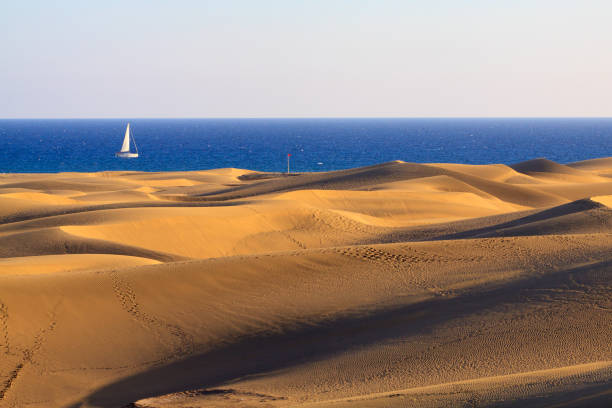 Dunes in Maspalomas the Gran Canaria island with the sailboat on ocean in background. stock photo