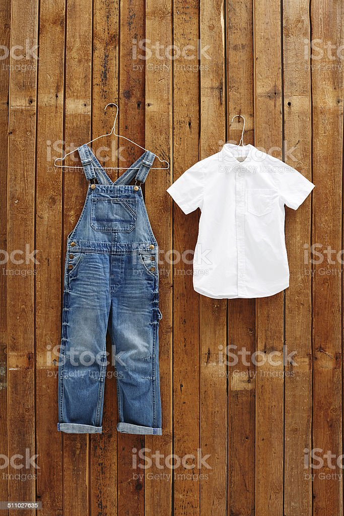 Dungarees and white shirt hanging against wooden background stock photo
