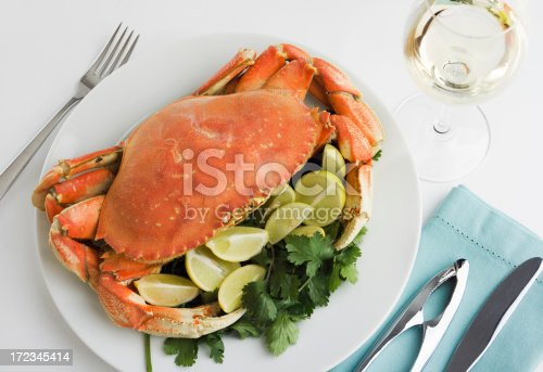 Dungeness crab seafood dinner, a cooked, prepared meal with slices of lemons and limes, served on a plate with a glass of white wine. Still life of the delicious, fresh food and drink is shown as a formal place setting including folded napkin and silverware on a white restaurant table.