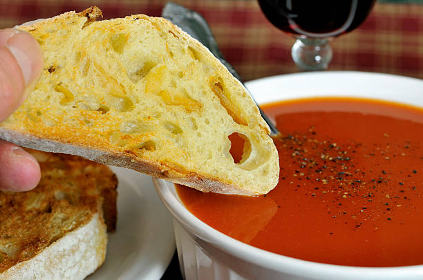 Dunking Bread in Tomato Soup stock photo