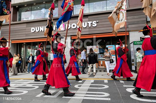 Seoul, South Korea - September 25, 2019: During the changing of the Royal Guard ceremony outside Deoksugung Palace in the heart of Seoul, people march past a Dunkin Donuts located across the street from the palace.