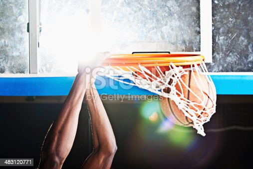 A black basketball player, doing a dunking. XXL size image. Image taken with Canon EOS 1 Ds Mark II and EF 70-200 mm USM L.