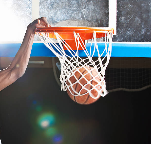 Dunking A basketball player, doing a dunking.  Image taken with Canon EOS 1 Ds Mark II and EF 70-200 mm USM L. slam dunk stock pictures, royalty-free photos & images