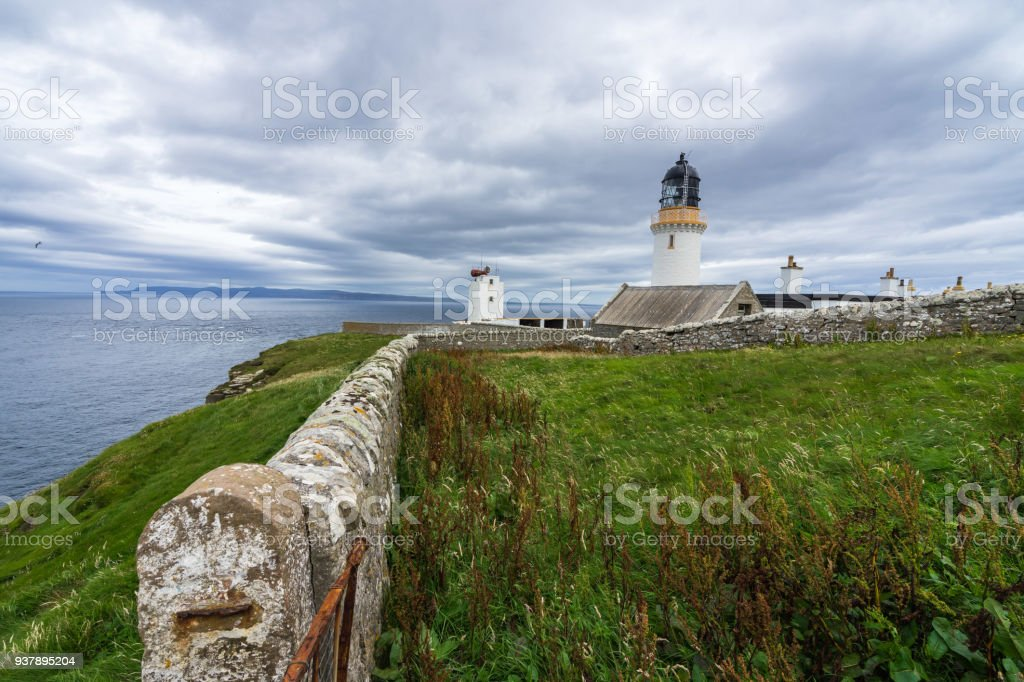Dunnet Head lighthouse on Pentland Firth with Orkney on the foreground, Scotland north coast, Britain stock photo