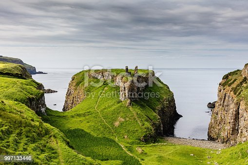Beautiful fresh green northern ireland coastal landscape towards the atlantic ocean with the gate lodge ruins on small peninsula at Dunseverick - Causeway Road, close to Giants Causeway. Dunseverick, Causeway Road, Giants Causeway, County Antrim, Northern Ireland, UK