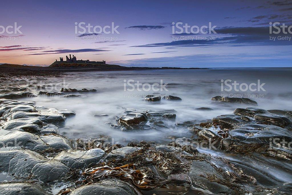 Dunstanburg Castle at dusk stock photo