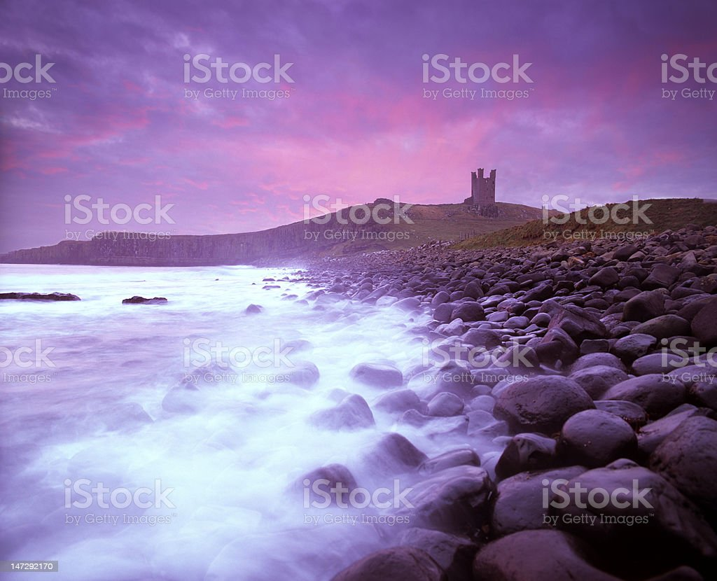 Dunstanburgh Castle at dawn, over boulderfield stock photo
