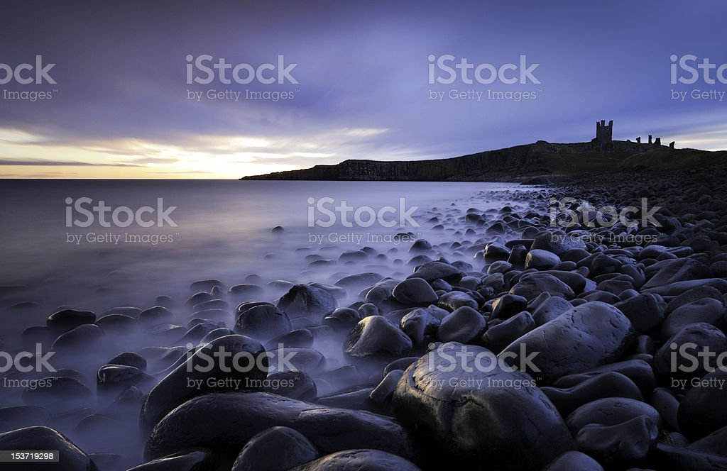 Dunstanburgh Castle over boulderfiled at Embleton Bay stock photo