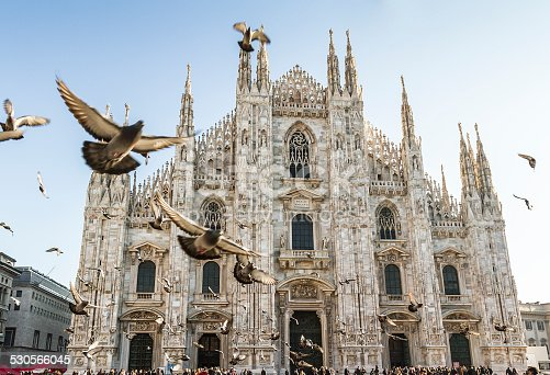 Duomo of Milan (Italy - Site of Expo 2015) with many pigeons in fly on forward