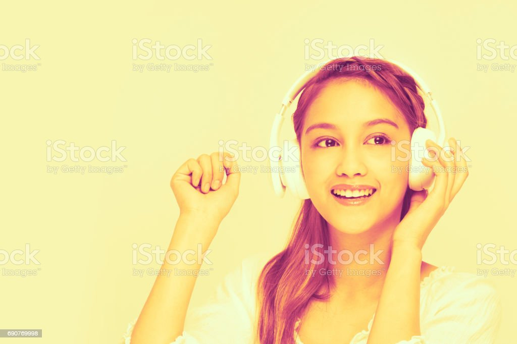 duotone of young woman listening music with wireless headphone, half latina and half asian stock photo
