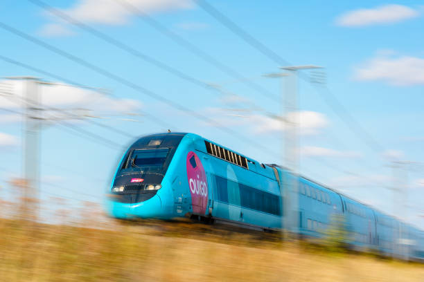 Un train à grande vitesse TGV Duplex en livrée Ouigo conduire à toute vitesse dans le paysage français. - Photo
