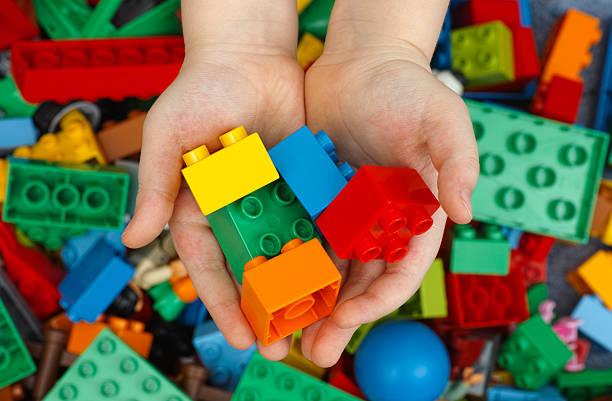 lego duplo bricks in childs hands - lego stockfoto's en -beelden