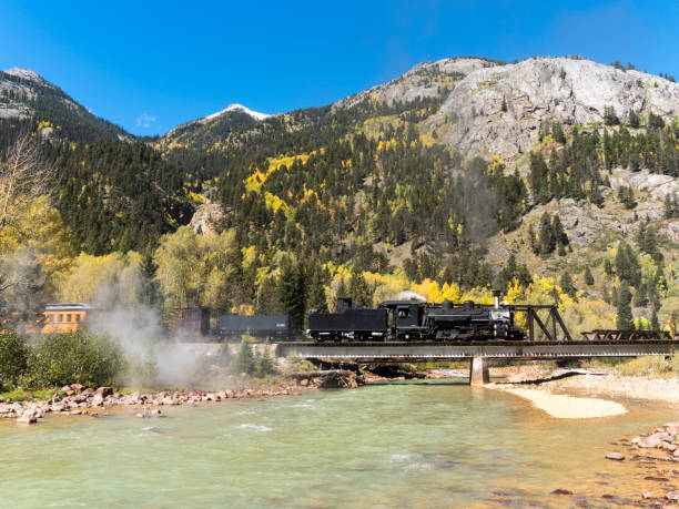 Durango Colorado Steam Locomotive Animas River Bridge San Juan Mountains The Durango & Silverton Narrow Gauge Railroad (D&SNG) travels between Durango, Colorado and Silverton, Colorado with its vintage steam locomotives. This is in the San Juan Mountains and near the Animas River. These great excursion passenger trains are enjoyed by a large number of people each day, with most starting from the Durango Depot. Photo edited to remove names and numbers. animas river stock pictures, royalty-free photos & images