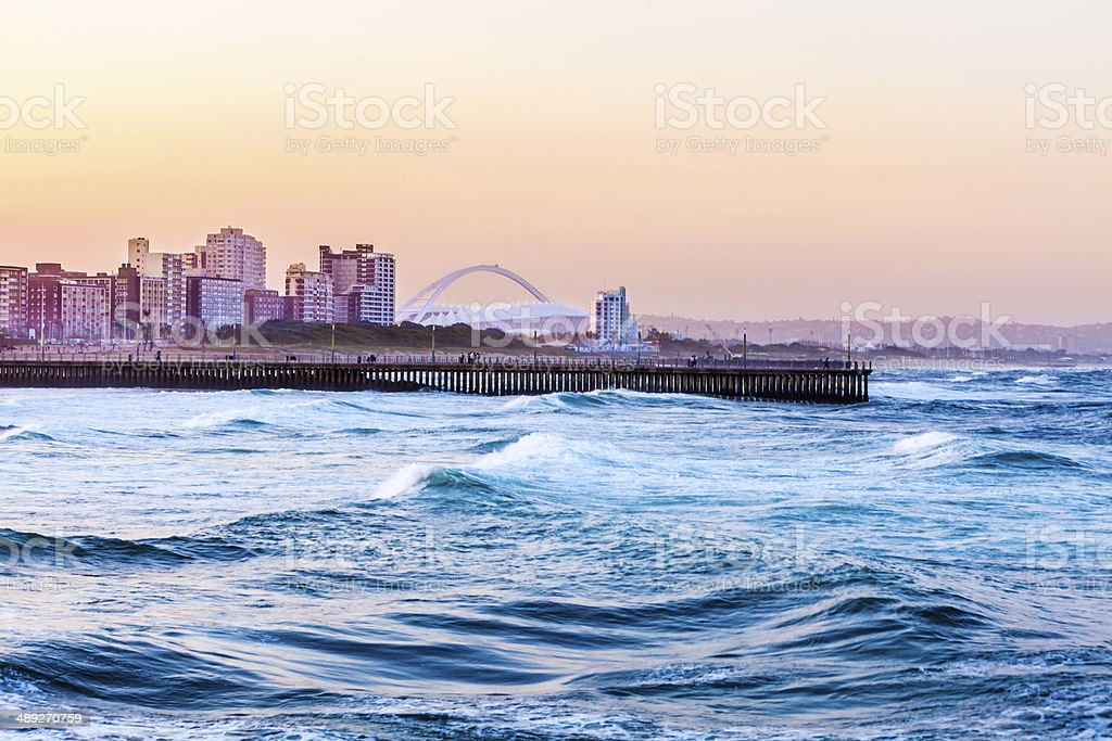 Durban seafront with world cup Stadium Durban evening sunset cityscape with stadium, Moses Mabhida Stadium, Kwazulu-Natal, South Africa, showing the pier on Durban beach. Chalet Stock Photo