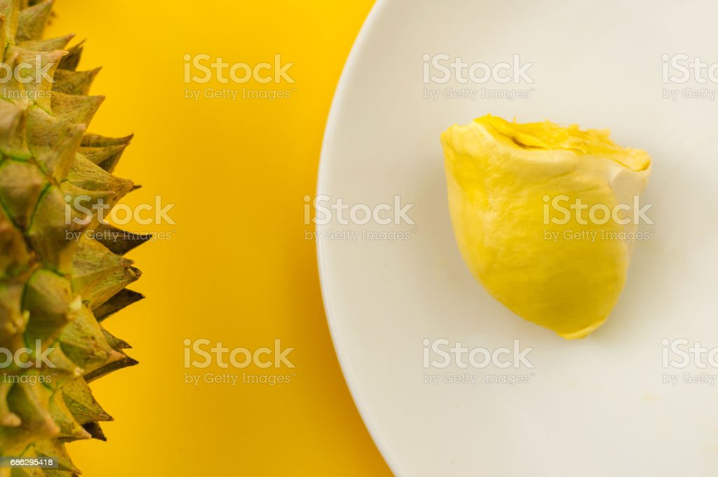 Durian on a white plate with green spike rind  and yellow background, king of the fruit but smelly in Thailand and south east asia; soft  focus stock photo