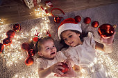 Adorable and cute sister, lying down surrounded with Christmas red ornaments and Christmas lights, and bonding during Christmas time in matchy-matchy dresses