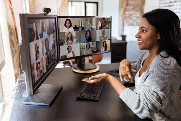 During COVID-19, attractive woman gestures during virtual meeting with colleagues stock photo