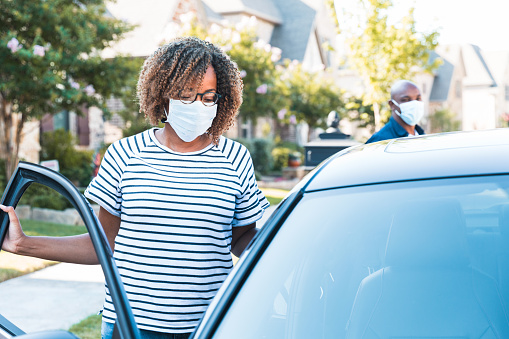 A mid adult woman wearing a protective mask gets in the passenger seat of her car.  Her husband, also wearing a protective mask, goes around to the driver's side.