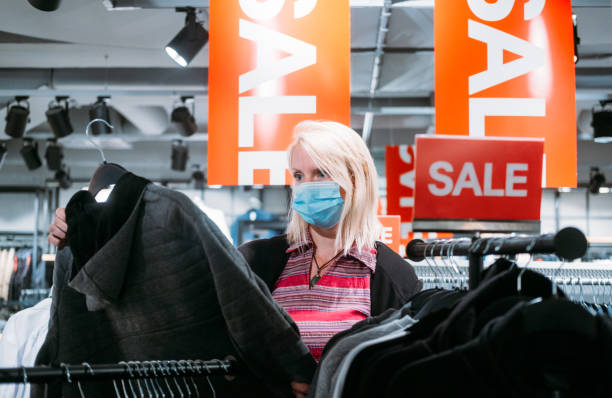 SALE during COVID-19 Close-up of a young woman wearing a protective face mask, while buying the clothes on a sale in a shopping mall.  Safety and a protection during the Coronavirus pandemic. discount store stock pictures, royalty-free photos & images