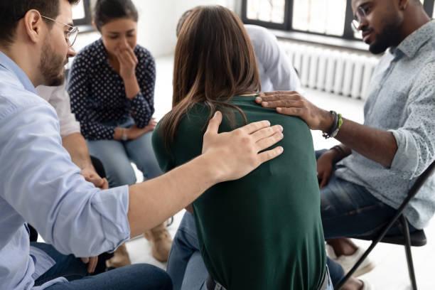 durante la sessione di terapia di gruppo i membri sostengono il pianto ragazza disperata - assuefazione foto e immagini stock