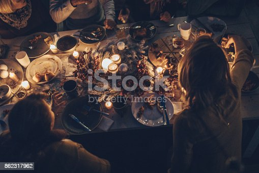 Photo of a multi generation family during Thanksgiving dinner, spending time together over eaten food and messy plates