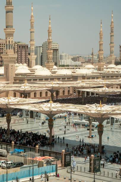 während des freitagsgebets beten tausende muslimischer pilger in der al-masjid an-nabawa moschee im zentrum der heiligen stadt medinah, ksa - zelt stehhöhe stock-fotos und bilder