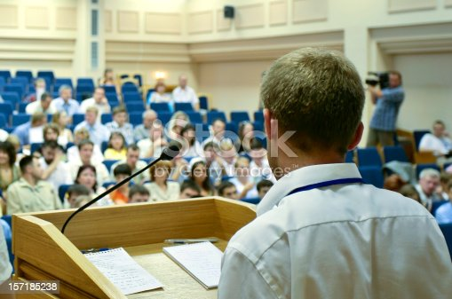 A man is making a speech in front of a big audience at a conference hall.