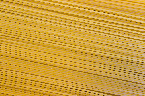 Farfalle bow tie wholewheat and durum wheat pasta. Butterflies shape uncooked food background. Italian and Mediterranean cuisine traditional ingredient, closeup, top view.