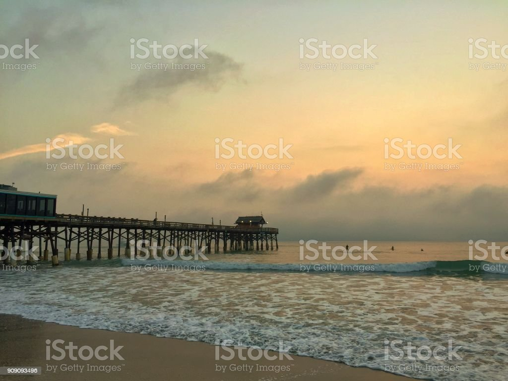 Dusk And The Setting Sun Cast A Magical Golden Hue Over A Pier