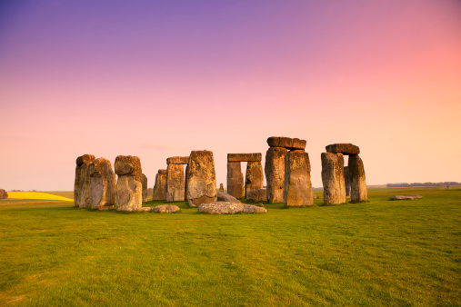 Ancient stones at UNESCO World Heritage Site at Stonehenge, Wiltshire, UK. Dramatic sky and golden hues of dusk. Major tourist destination, archeological and pilgrimage site during Summer Solstice and Winter Solstice.