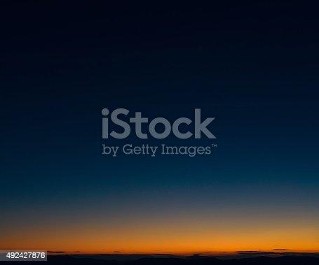 Dark blue sky above the orange glow above a distant horizon at dusk.