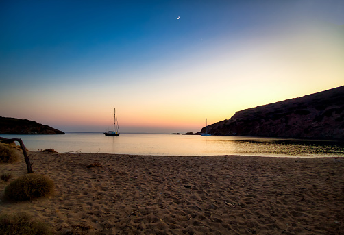 Dusk in Andros island with moon and sailboat silhouette. Cyclades, Greece