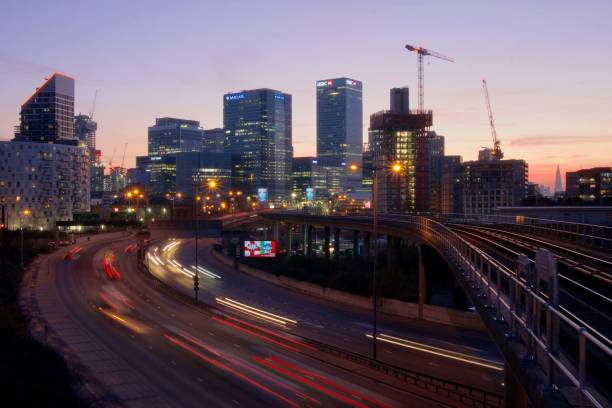 Dusk looking towards Canary Wharf, London View from East India DLR station, looking towards Canary Wharf. With traffic light trails in the foreground. skeable stock pictures, royalty-free photos & images