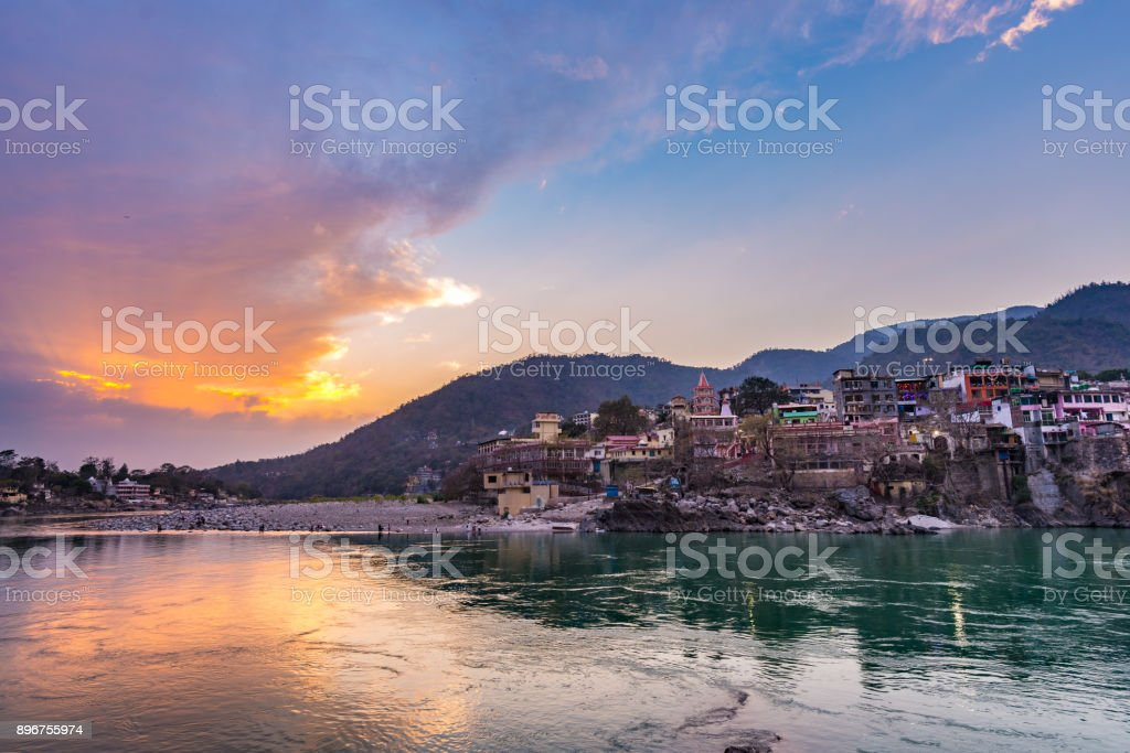 Dusk time at Rishikesh, holy town and travel destination in India. Colorful sky and clouds reflecting over the Ganges River. stock photo
